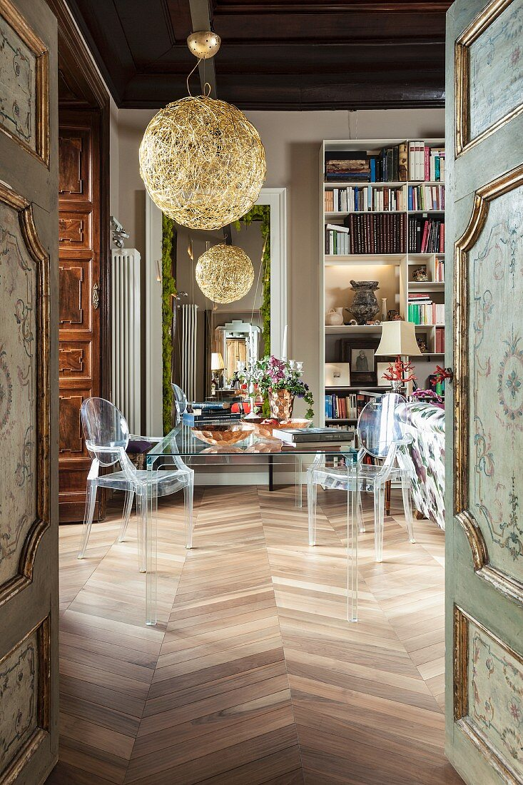 View of transparent furniture in library seen through antique, painted, panelled doors