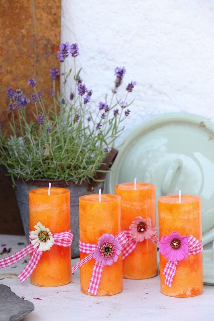 Orange candles decorated with flowers and ribbons