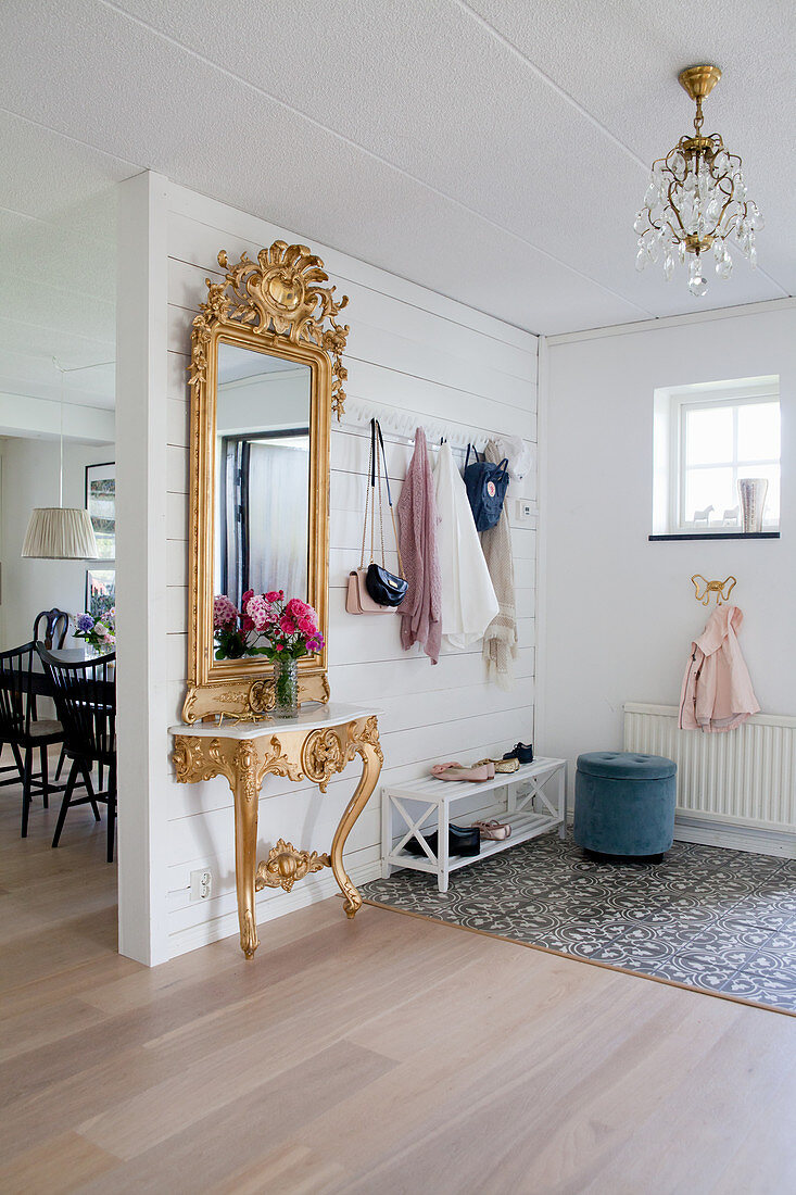 Baroque gilt-framed mirror and console table in hallway