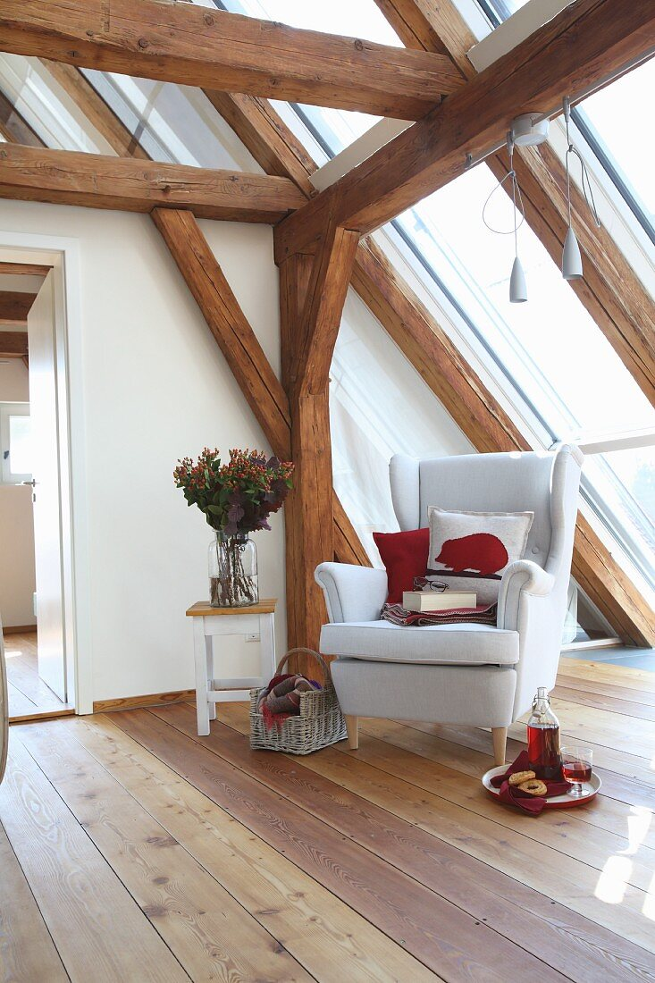 White wing-back chair and cushion with red felt hedgehog motif in cosy reading corner in converted attic