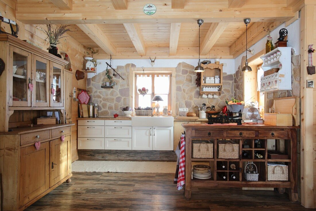 Dresser, island counter and one stone wall in open-kitchen of wooden cabin