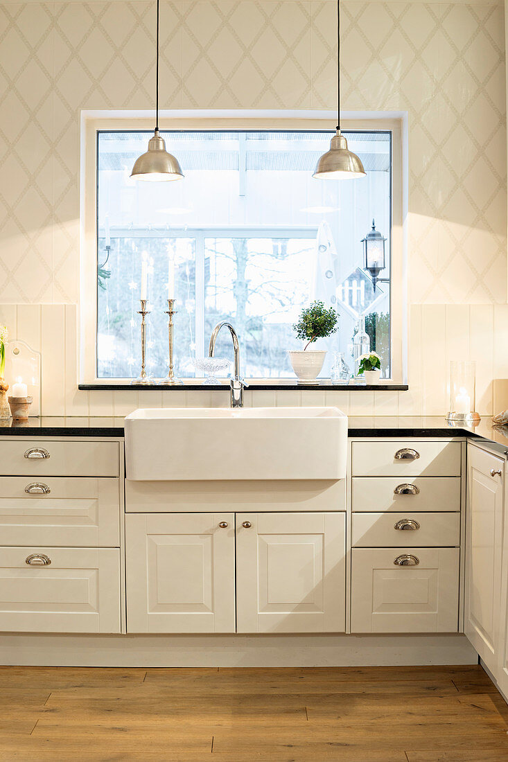 White country-house kitchen with diamond-patterned wallpaper and large window