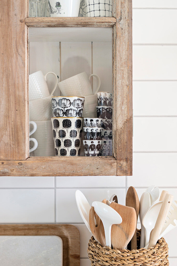 Basket of wooden spoons below black and white mugs in glass-fronted cabinet