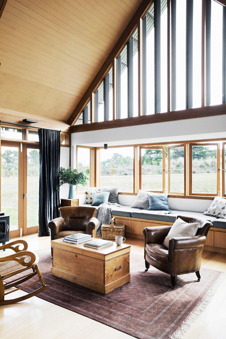 Cozy, high living area with leather armchairs and wooden chest in front of glazed gable wall