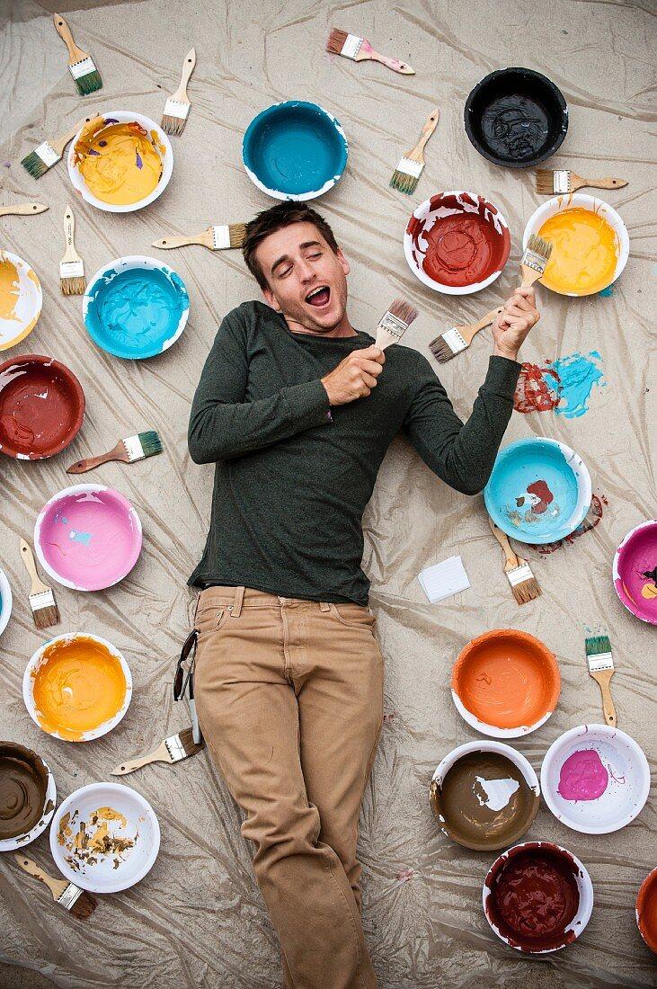 Man holding paintbrushes lying on tarpaulin amongst paint pots