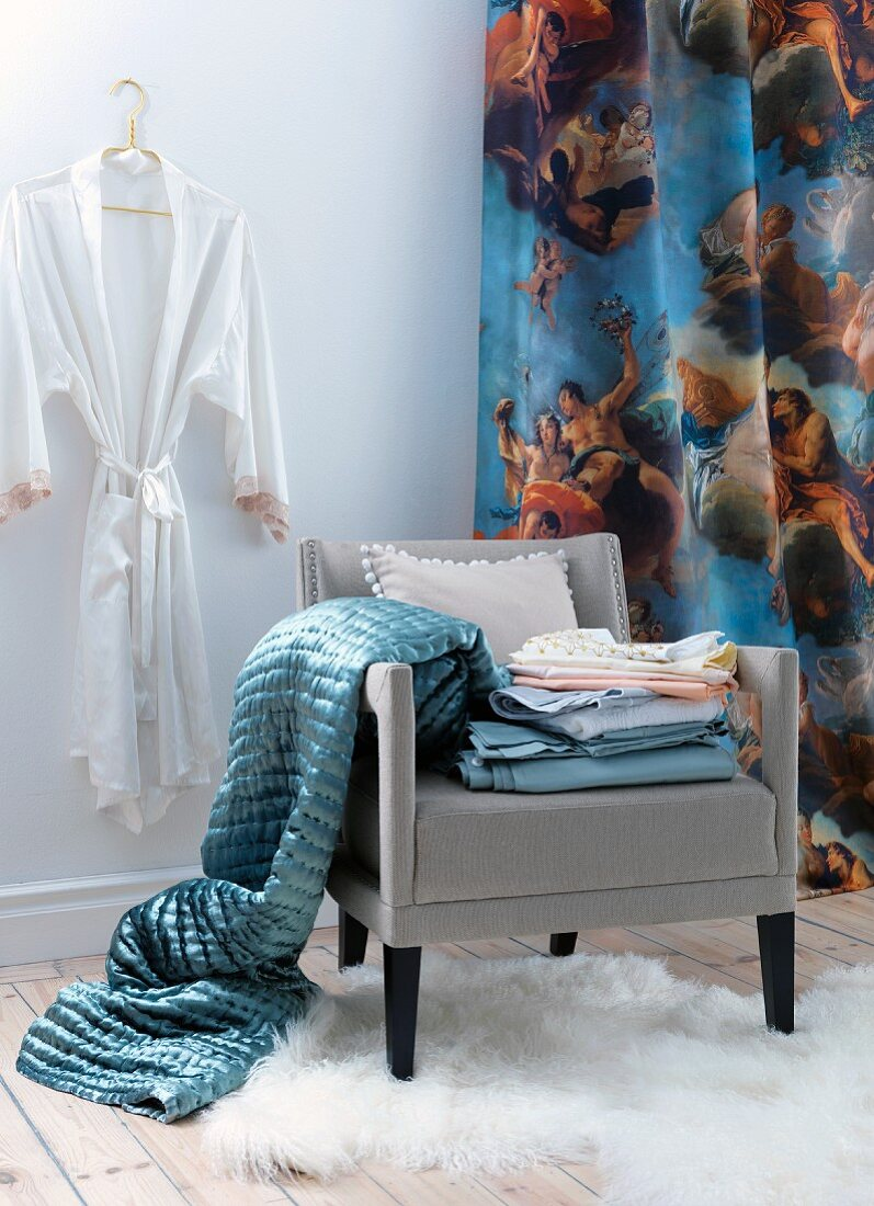 Dressing corner in white room with blue blanket and bed linen on chair