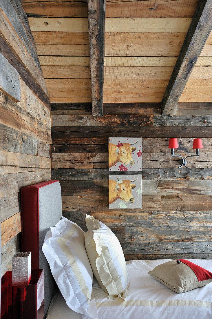 Bilder mit Kühen über dem Bett im rustikalen Schlafzimmer