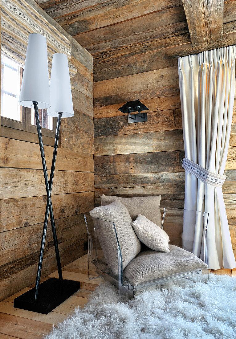 Moderner Acrylsessel mit Kissen vor rustikalen Holzwänden