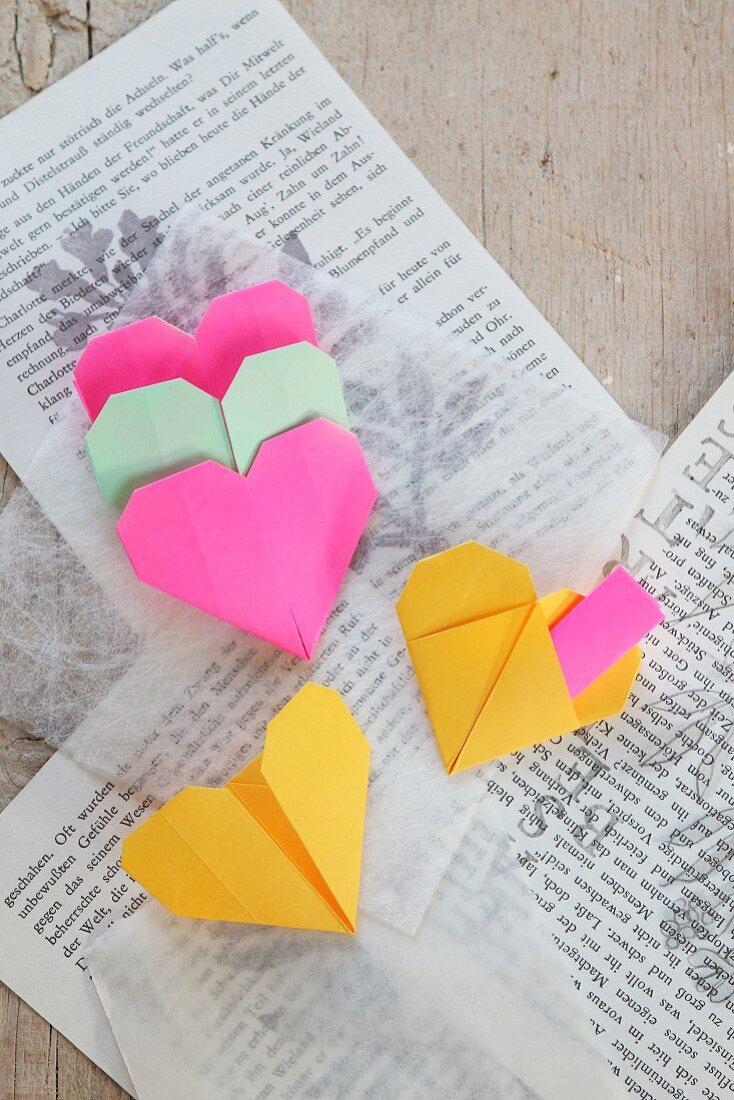 Origami-Herzen auf Buchseiten und transparentem Seidenpapier