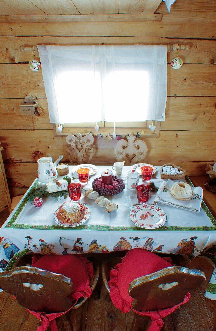 Weihnachtlich gedeckter Tisch in einer rustikalen Holzhütte