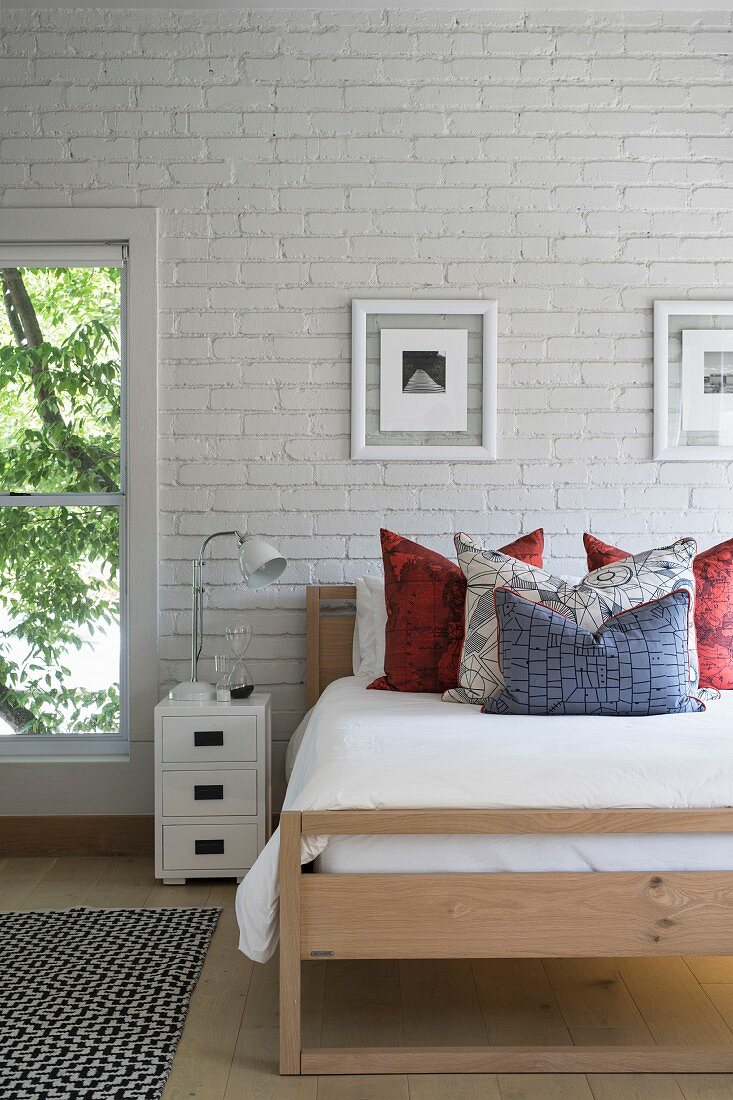 Modern wooden bed against white brick wall