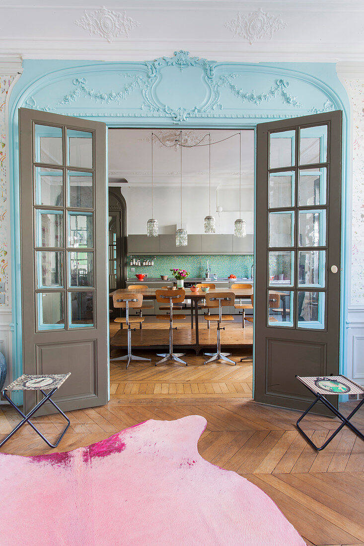 View into kitchen through double lattice doors painted blue and grey