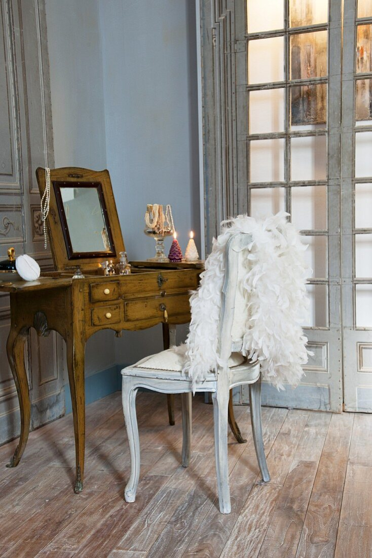 Antique dressing table and white feather boa on chair