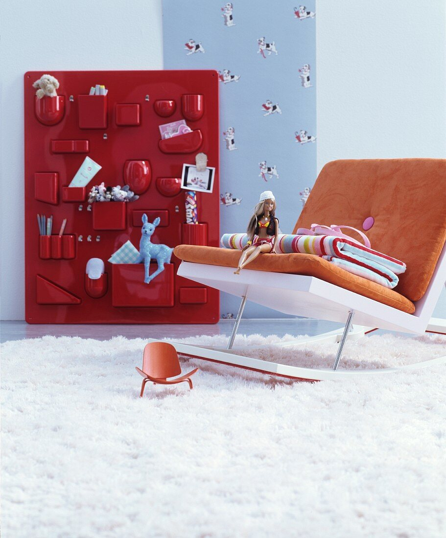 Modern rocking chair in front of toys in red organiser on wall