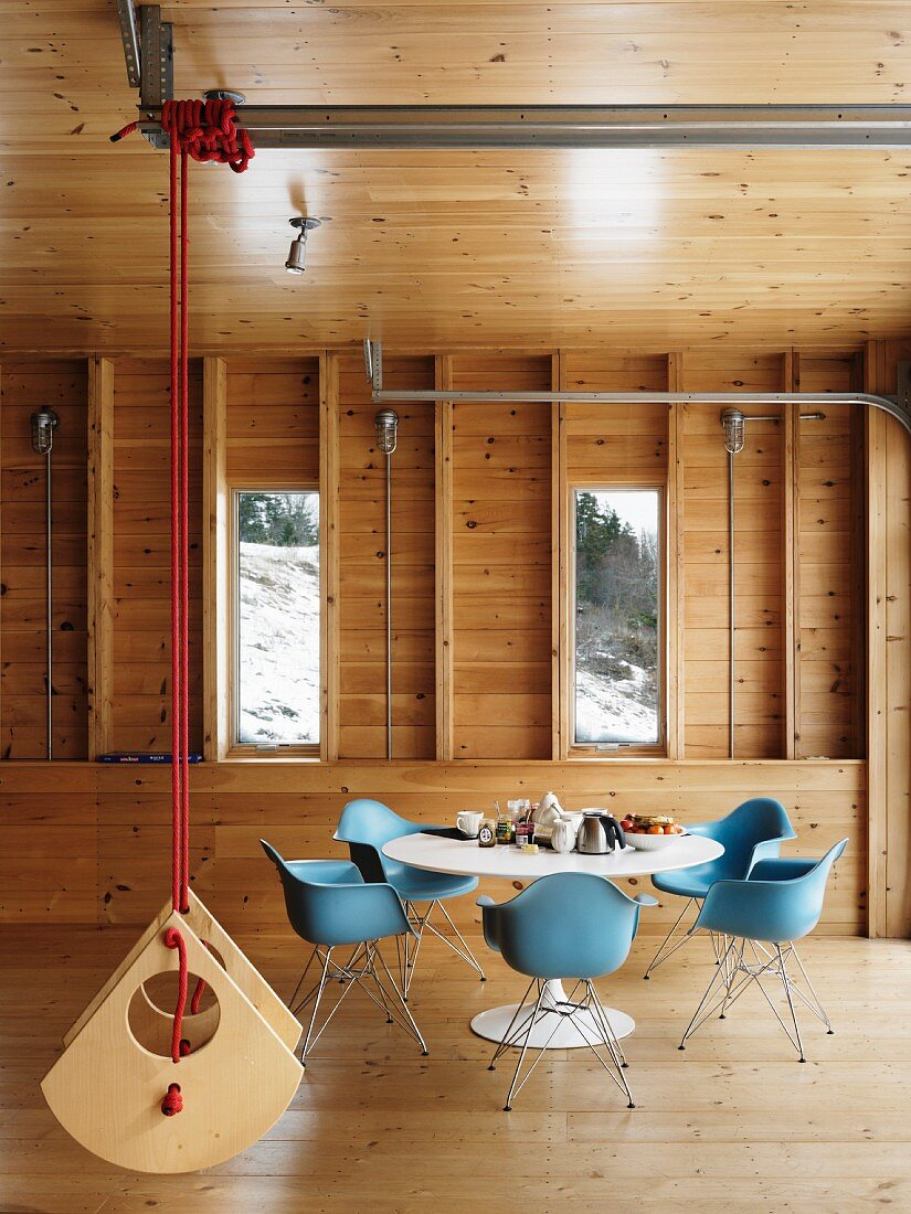 Classic dining set and suspended designer swing in wooden house
