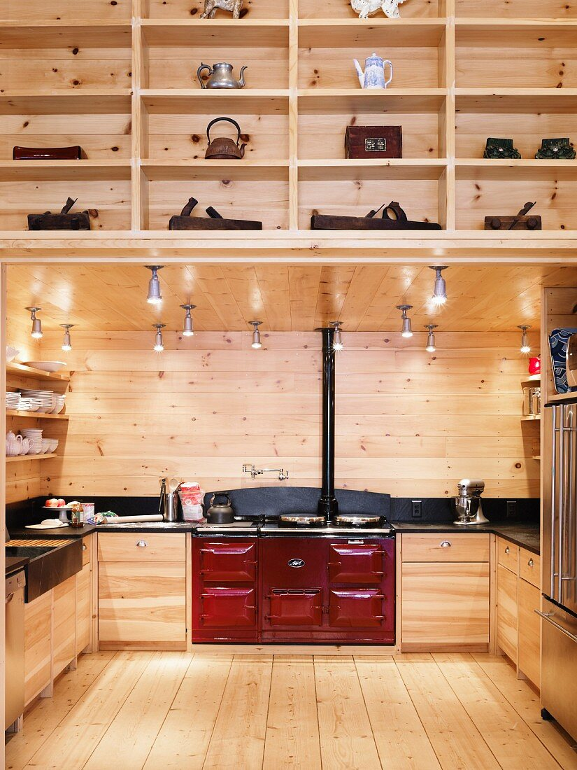 Illuminated fitted wooden kitchen with red AGA cooker in wooden house with fitted shelving in foreground