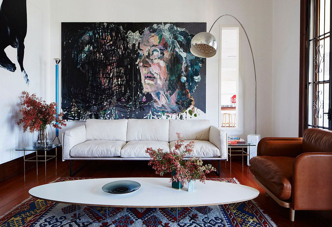 Classic, oval coffee table, couches, arc lamp and large format painting in the living room
