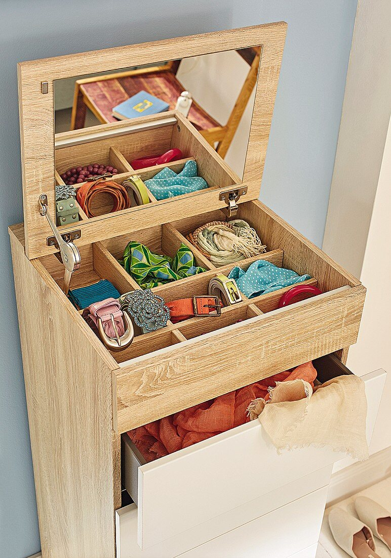 A chest of drawers with organiser compartments and a mirror inside the lid