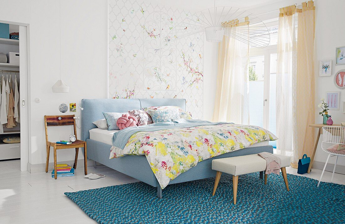 A padded double bed and bench on a turquoise rug in a light, bright bedroom