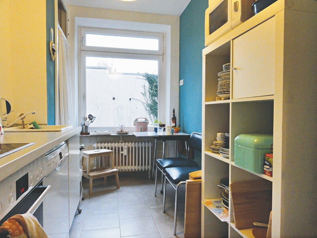 A unit and open shelf in a kitchen with a table and chairs in the background