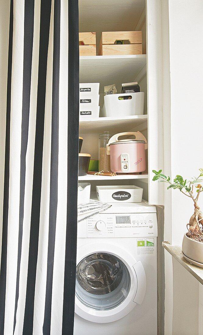 Abstellkammer mit Waschmaschine hinter gestreiftem Vorhang