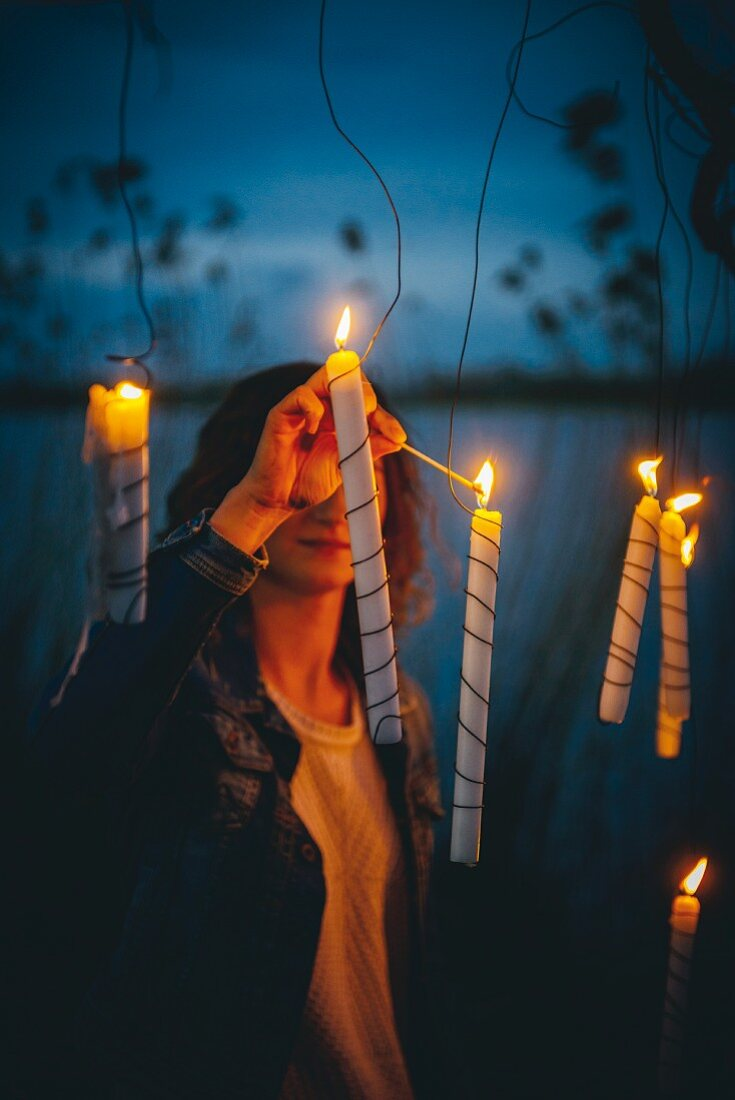 Woman lighting candles outside