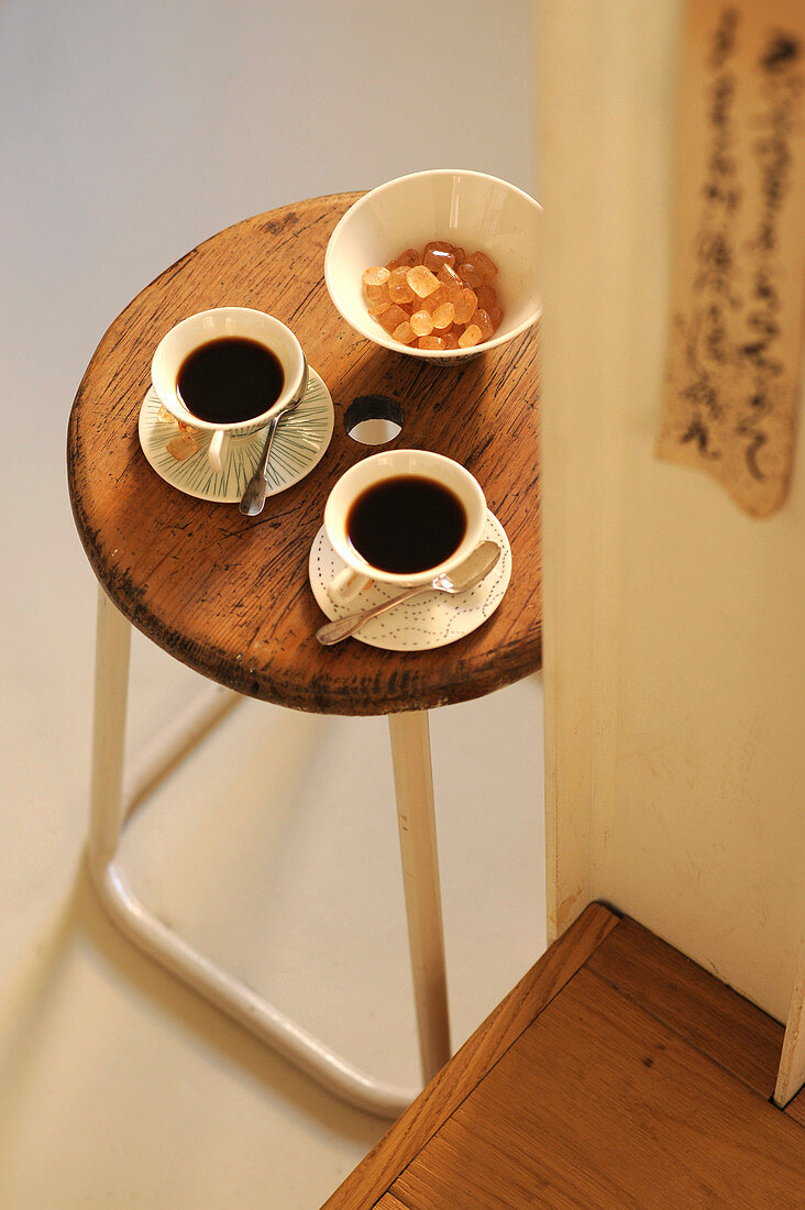 Two cups of coffee and bowl of sugar on retro stool