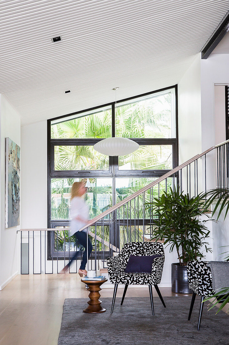 Armchairs and side table in front of stairs