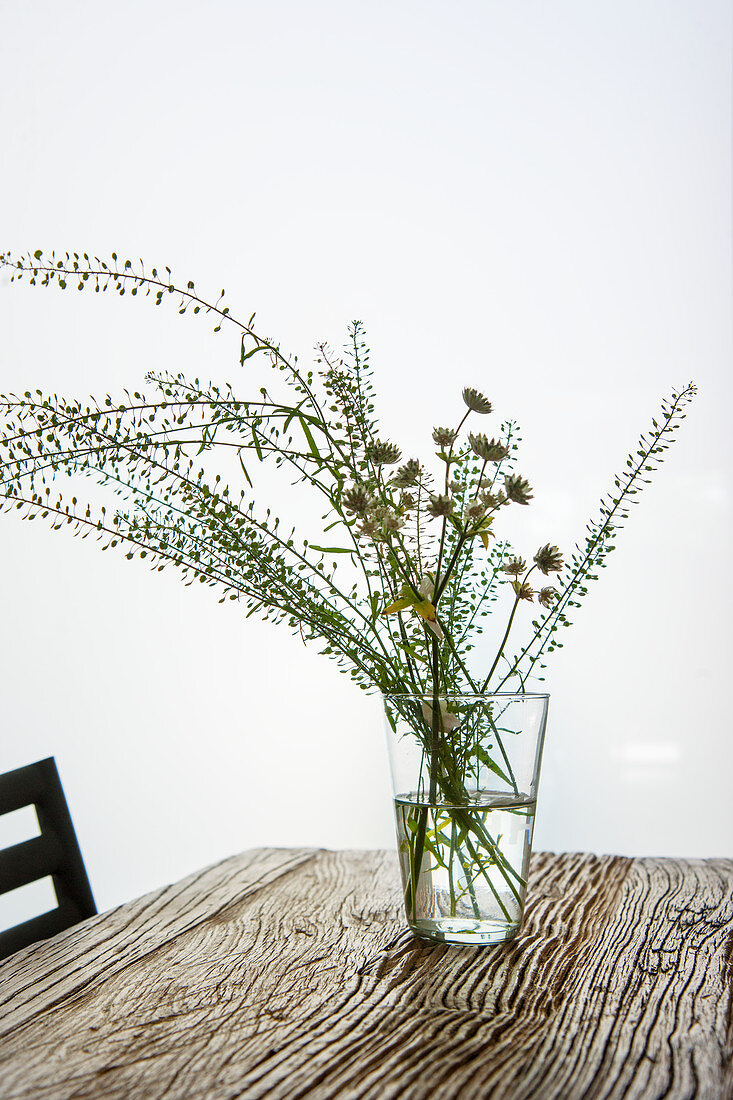 Wild flowers in glass of water on weathered wooden table