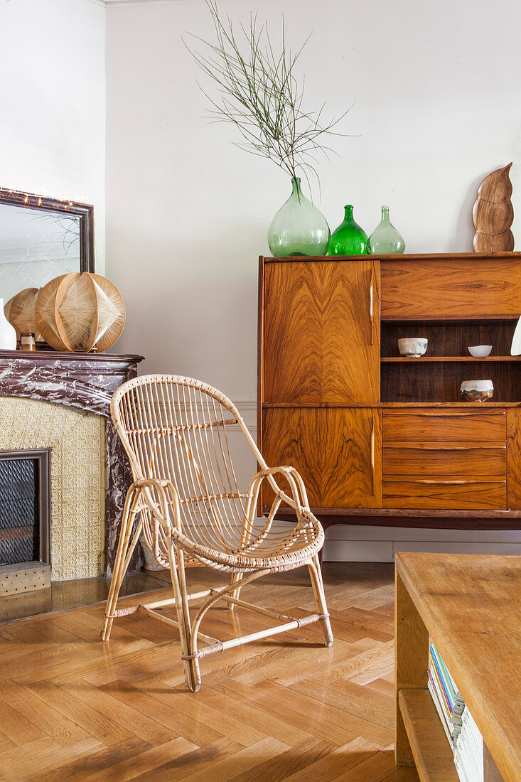 Rattan armchair in front of old cabinet with veneer front