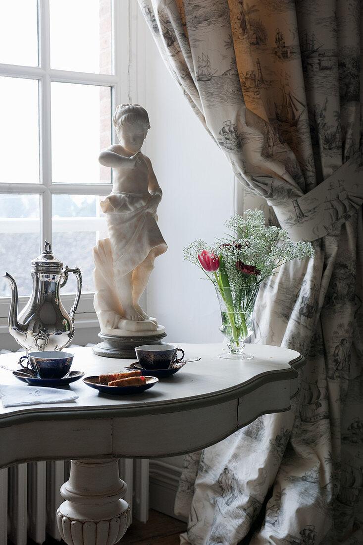 Breakfast crockery on table with baluster leg below window