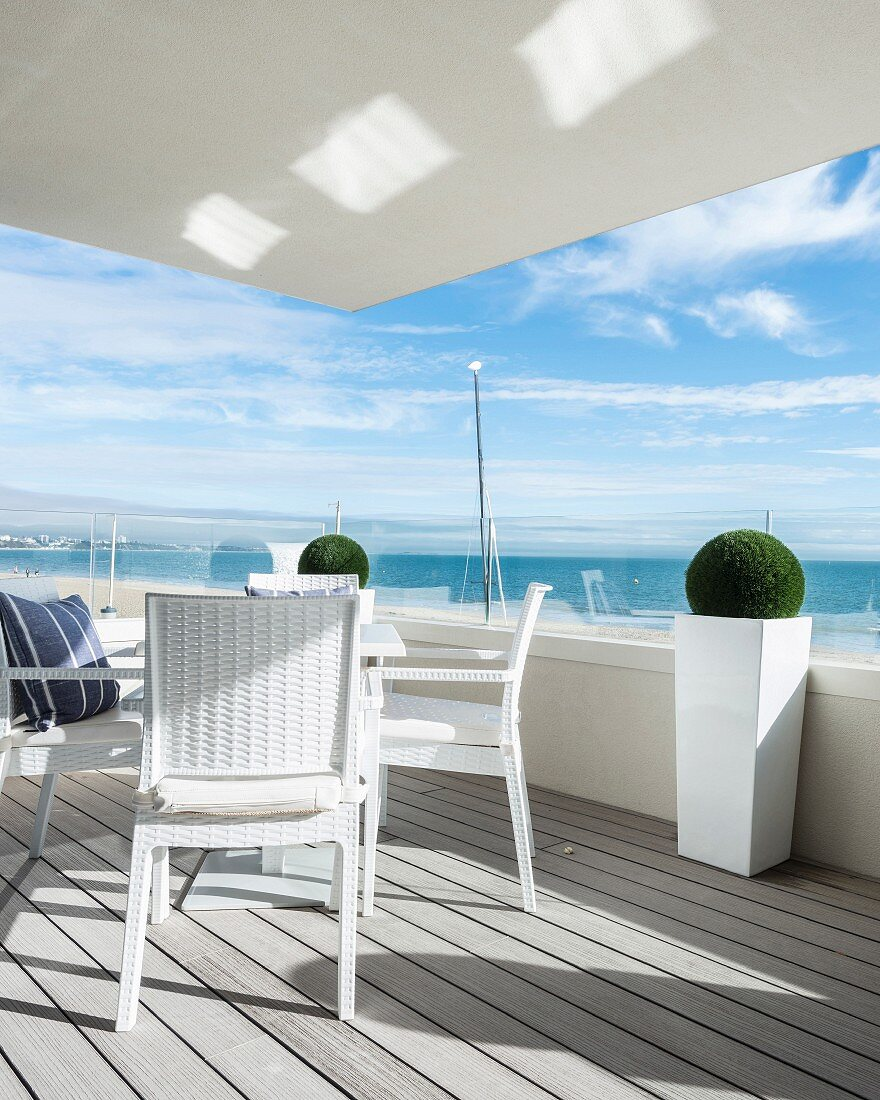 White outdoor furniture on balcony with glass balustrade and sea view