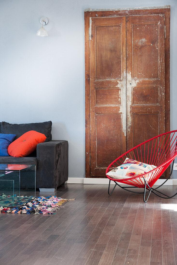 Red designer easy chair in front of worn wooden door in living room