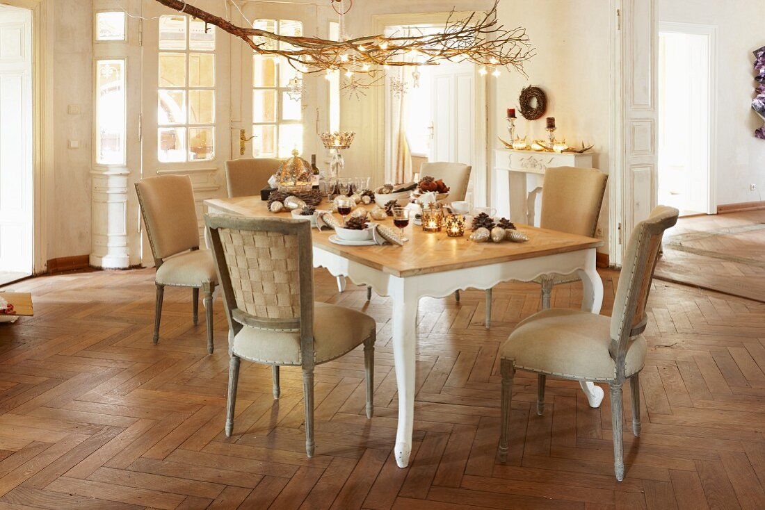 Christmas tree in period interior with herringbone parquet floor and set dining table