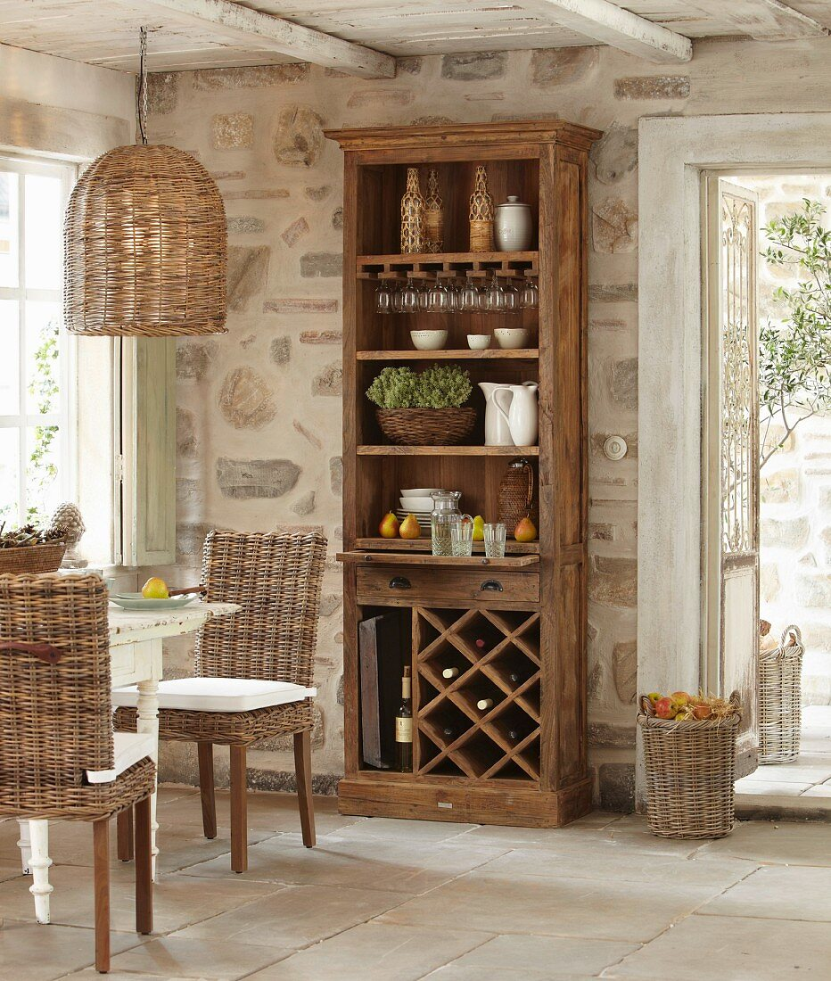 Crockery in cabinet with shelves and wine rack against stone wall in rustic dining area