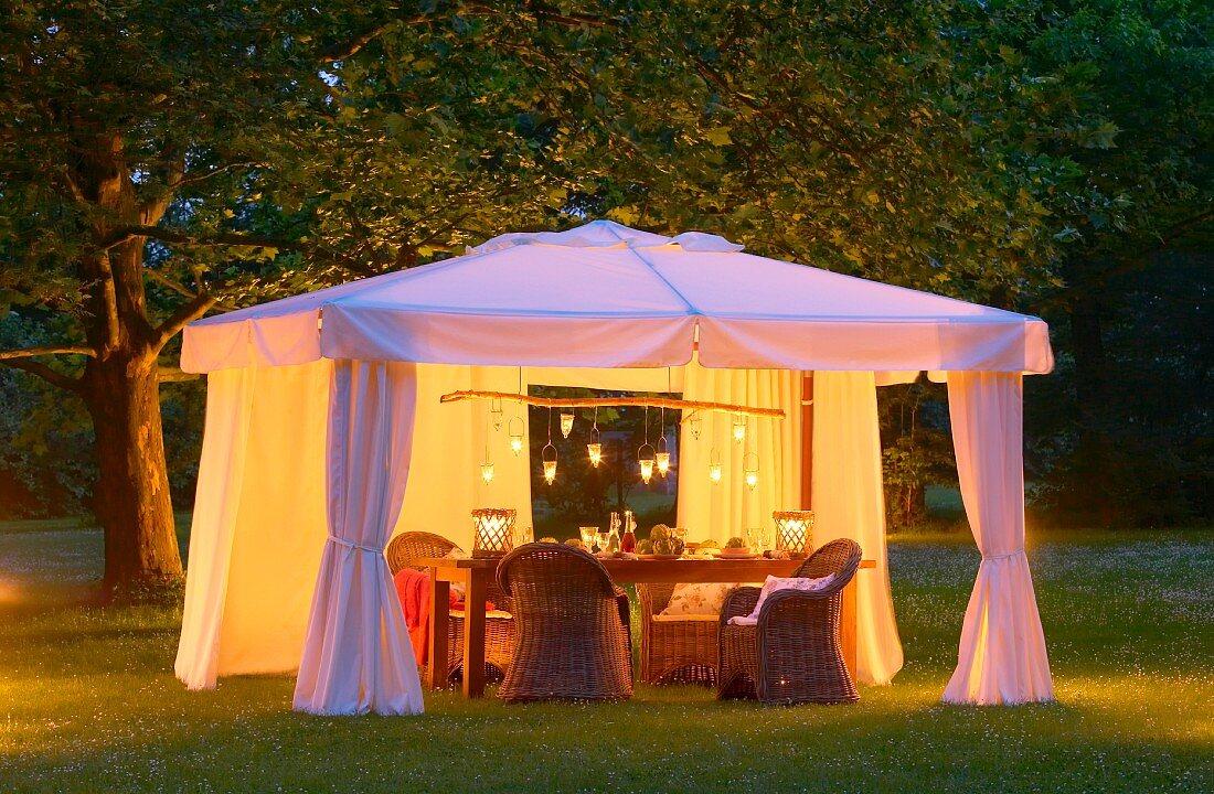 Wicker furniture in elegant, candlelit white pavilion on twilit summer lawn