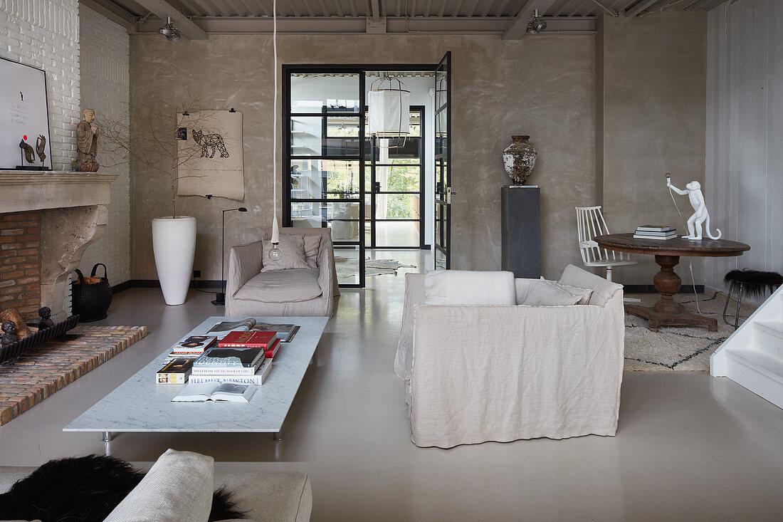 Loft-Wohnzimmer in Schlammtönen, Hussensessel und Couchtisch vor Kamin