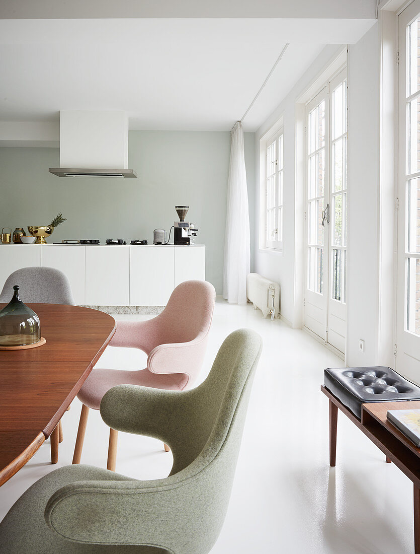 Chairs with pastel upholstery in front of modern open-plan kitchen