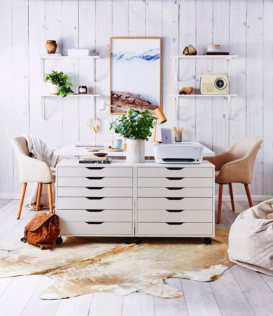 Home office with two white drawer containers, desks and wall brackets on a wooden wall