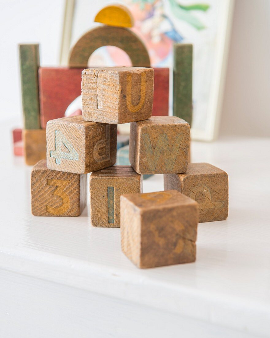 Letters and numbers on worn, stacked wooden building blocks