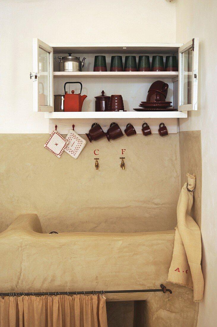 Traditional sink below crockery on wall-mounted shelves