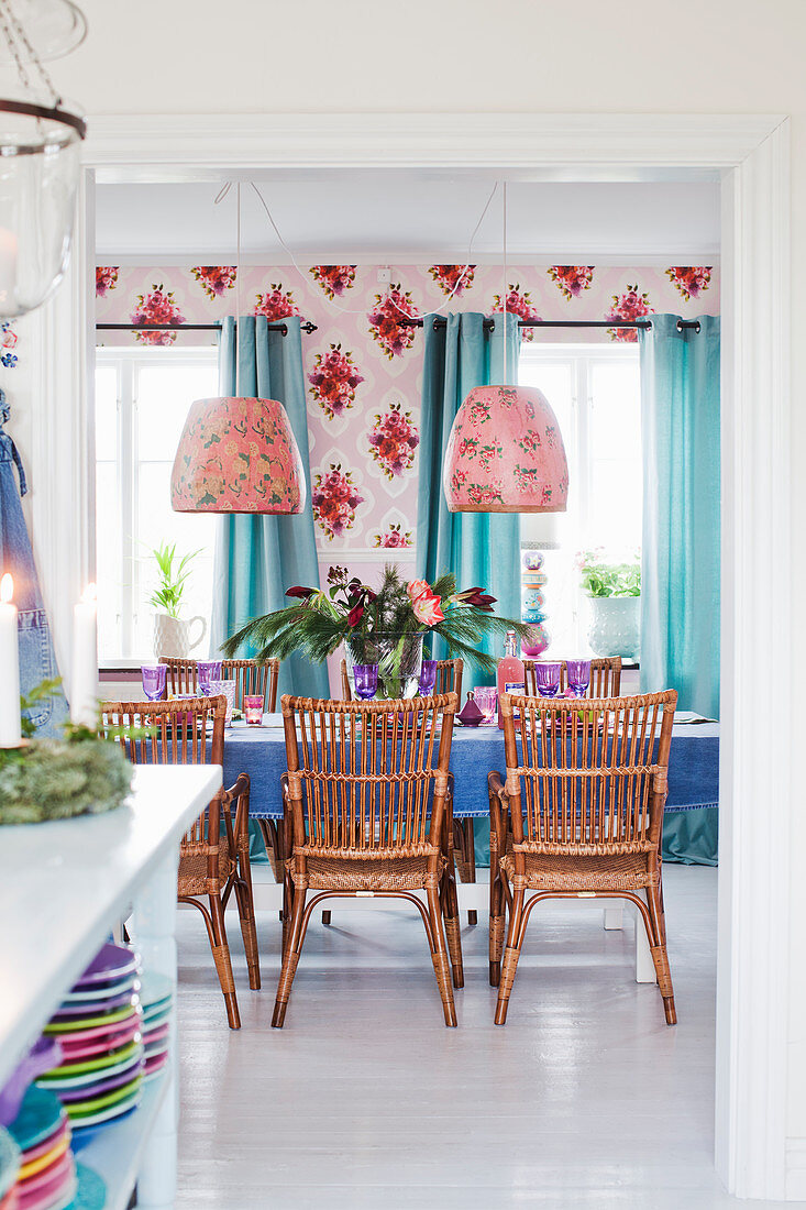 Rattan chairs around brightly set dining table in front of wallpaper with bold floral pattern