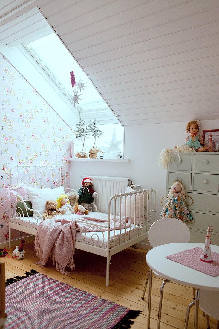 Bed with metal frame below skylight in girl's bedroom