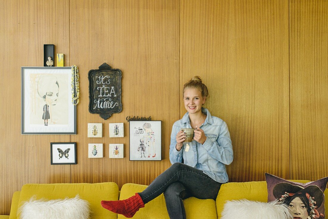 Young woman sitting on backrest of sofa next to small gallery of pictures