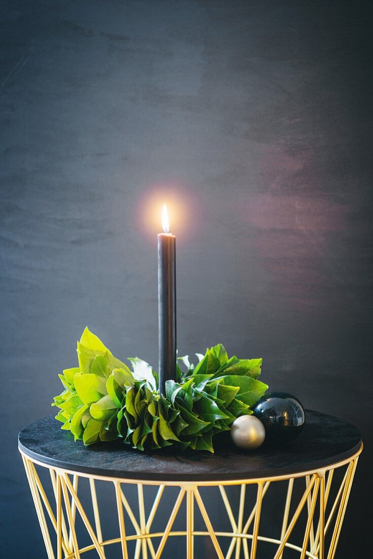 Lit black candle in hand-made wreath of leaves
