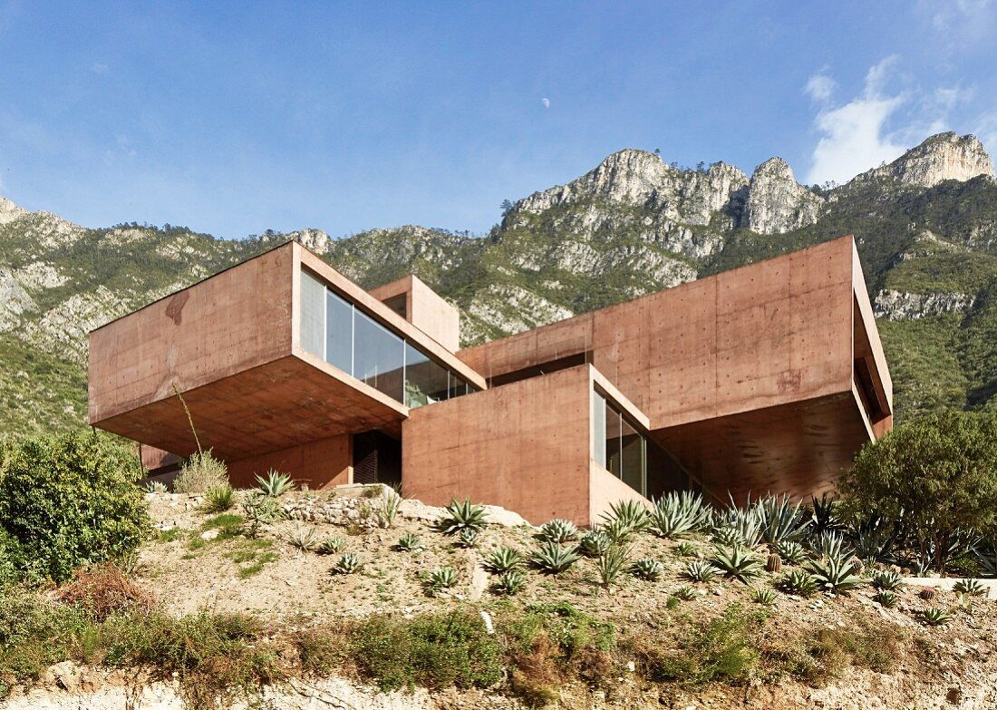 Modern architect-designed house made from red concrete in mountain setting