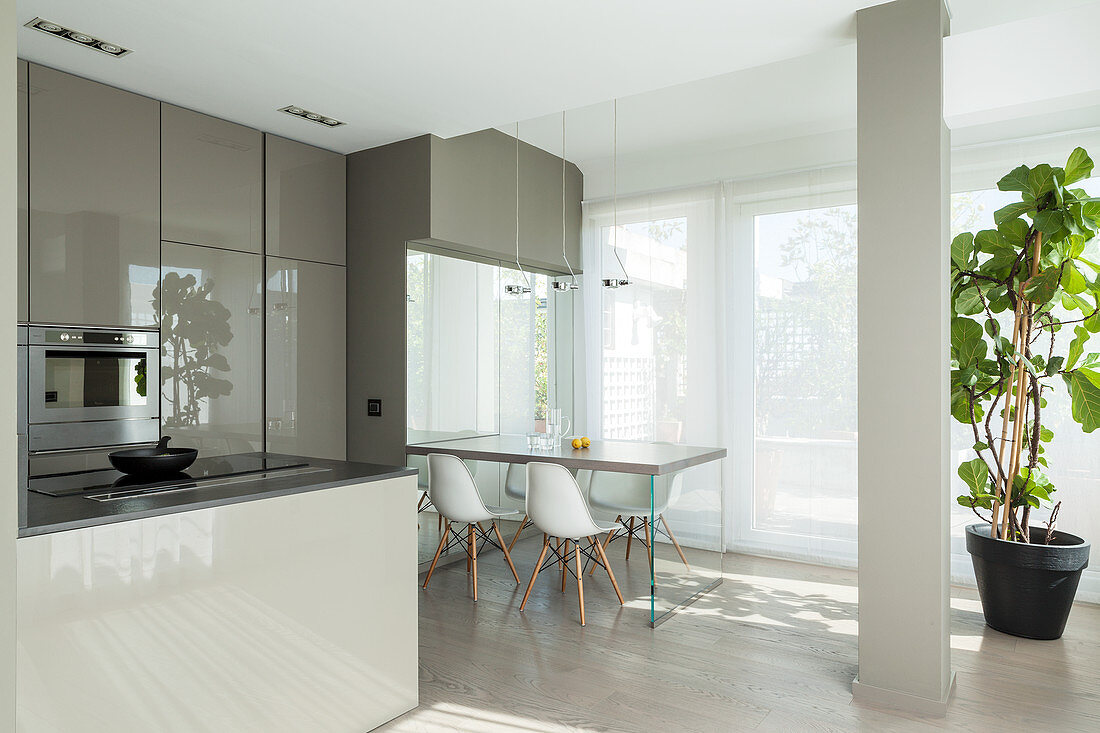 Breakfast table and classic chairs next to glass wall in designer kitchen