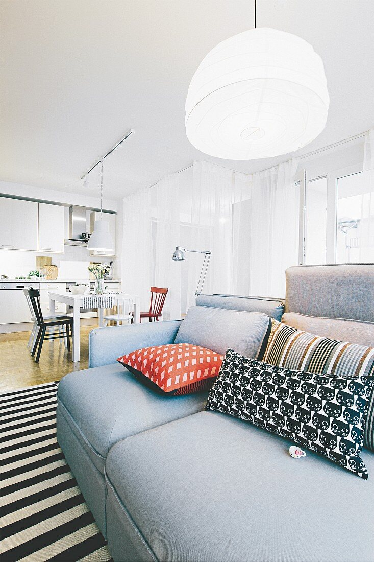 A grey sofa with cushions on a black-and-white striped rug in a light, bright open-plan living area
