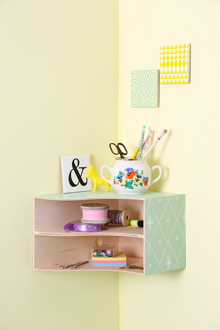 Small, wall-mounted, corner shelf unit made from box files covered in decorative paper