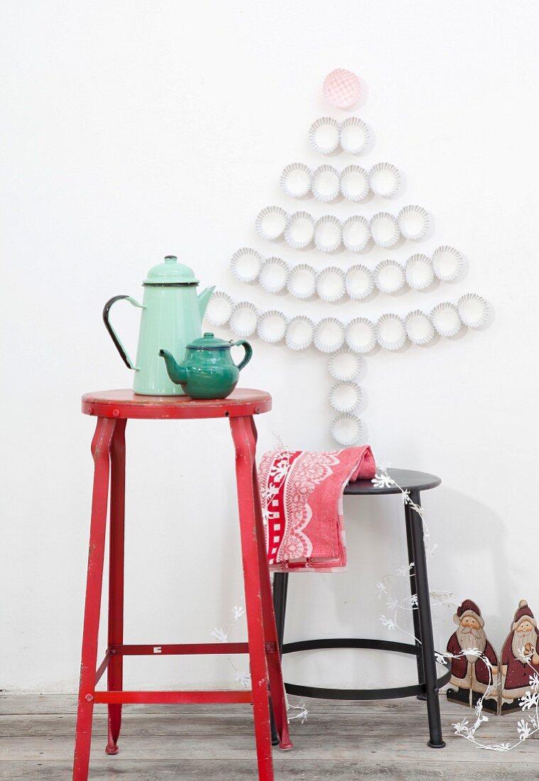 Tannenbaum-Silhouette aus aufgeklebten Papier-Muffinförmchen an weißer Wand